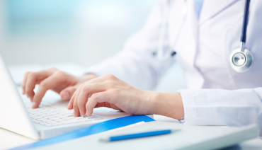 On The Blog: 4 Ways your EHR can help improve clinical efficiency. Photograph of a doctor using a laptop to enter charting data.